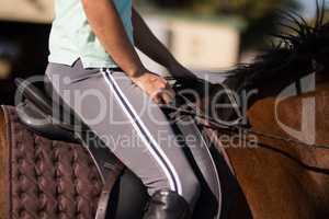 Mid section of female jockey sitting on horse