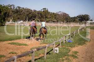 Female friends horseback riding at paddock