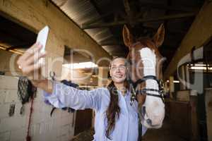 Smiling vet taking selfie with horse in stable