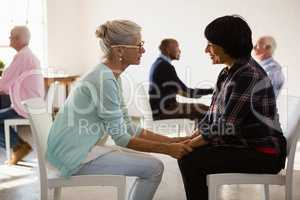 Side view of senior friends holding hands while siting on chair