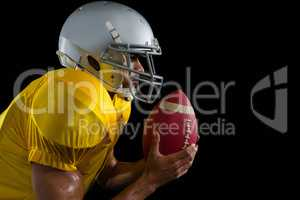 American football player holding a ball close to his face