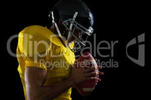 American football player holding a football with both his hands