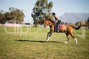 Side view of female jockey horseback riding