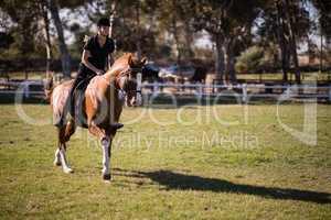 Jockey riding horse at equestrian center