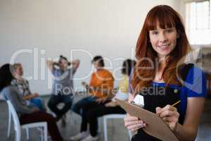 Portrait of smiling teacher holding clipboard with students talking in background