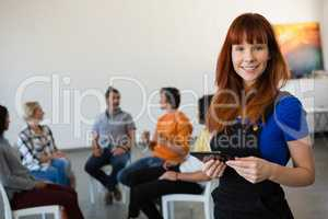 Portrait of happy teacher holding digital tablet with students talking in background