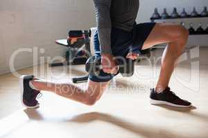Low section of male athlete exercising lunges in club