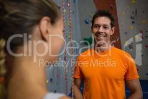 Smiling trainer talking to female athlete at health club