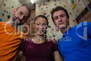 Portrait of confident male trainer with athletes in health club