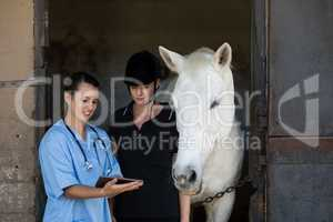 Vet showing digital tablet to jockey while standing by horse
