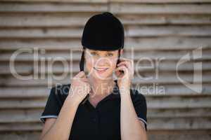 Portrait of smiling female jockey adjusting sports helmet