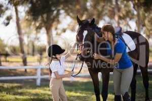 Happy girl and female jockey stroking horse