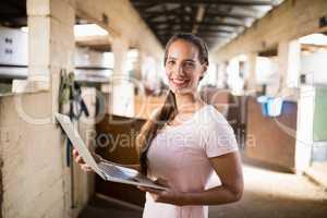 Portrait of smiling female jockey holding laptop