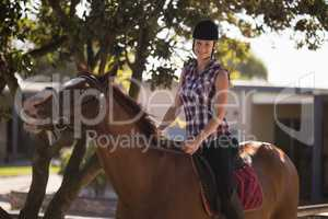Portrait of happy female jockey sitting on horse