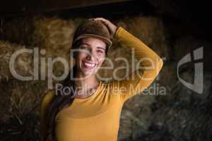 Portrait of happy female jockey in stable