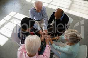 High angle view of senior friends stacking hands