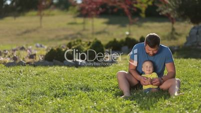 Positive dad playing with cute infant boy on grass