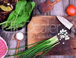 Chopped green onion on a wooden kitchen board