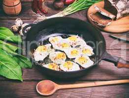 Fried eggs  in a black frying pan