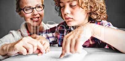 Teacher with boy using braille to read