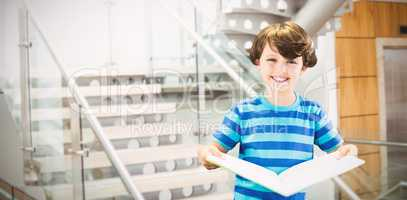 Composite image of portrait of smiling boy holding book