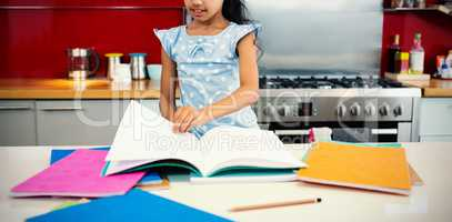 Girl flipping pages of book in kitchen