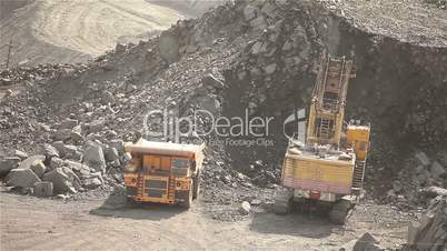 Work excavator in the quarry, sunny day, good weather, dump truck
