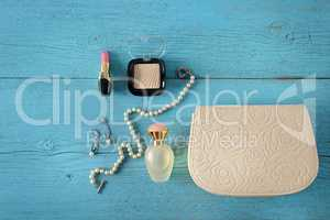 Cosmetics, perfumes, jewelry made of pearls and handbag on an ol