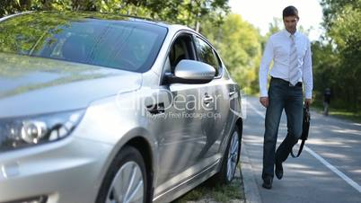 Stylish business executive getting into luxury car