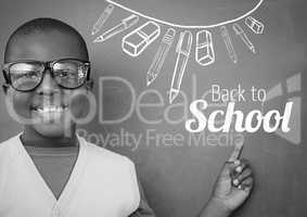 Back to School text and stationery on blackboard with boy