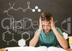 Worried student boy at table reading against grey blackboard with school and education graphic