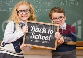 back to school text on blackboard with two school kids