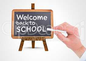 Hand writing Welcome back to school text on blackboard
