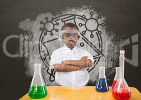 Student boy at table against grey blackboard with school and education graphic