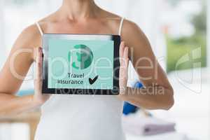 Woman holding a tablet with travel insurance concept on screen