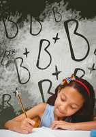 Student girl at table writing against green blackboard with school and education graphic