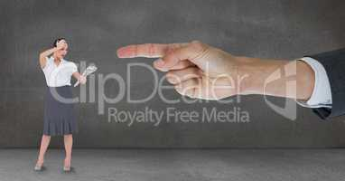Hand pointing at surprised business woman against grey background