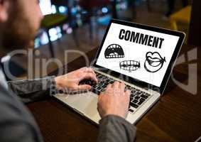 Comment text and cartoon mouth graphic on laptop screen with mans hands