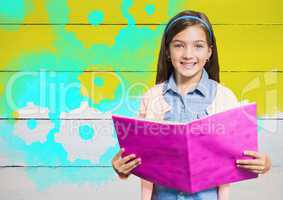 Girl holding book in front of yellow painted wall with cog gear settings