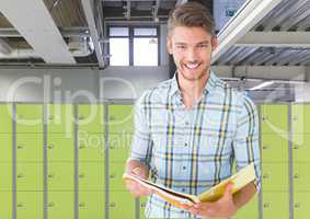male student holding book in front of lockers