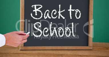 Hand writing back to school text on blackboard
