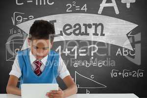 Student boy at table using a tablet against green blackboard with learn text and education and schoo