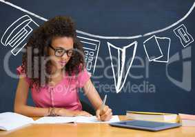 Student girl at table writing against blue blackboard with school and education graphic