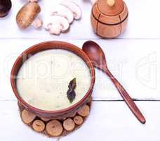 Creamy mushroom soup in a brown round plate