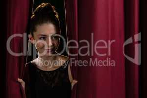 Ballet dancer peeking through a stage curtain