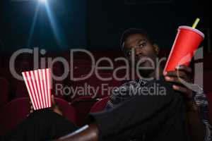 Man having popcorn and cold drink while watching movie