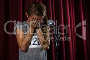 Girl covering her face with hand on stage