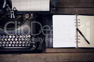 Typewriter by fountain pen on open diary