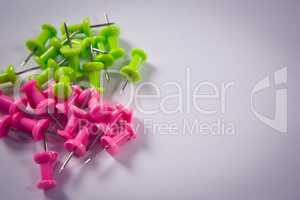 Pink and green push pins on white background