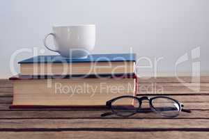 Books with cup of coffee and spectacles on wooden table